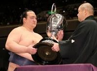 表彰式で日本相撲協会の八角理事長から賜杯を受け取る稀勢の里(左)=東京・両国国技館で2017年1月22日、佐々木順一撮影