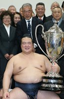 Kisenosato smiles with the Emperor's Cup in the dressing room at Tokyo's Ryogoku Kokugikan sumo venue on Jan. 22, 2017. (Mainichi)