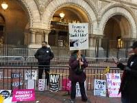 トランプ氏が昨年開業したホテル前で、抗議のプラカードを掲げる女性。周囲にはデモで使われた紙などが置かれていた=ワシントンで2017年1月21日、長野宏美撮影
