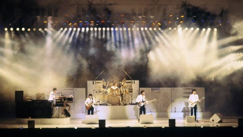 日本武道館のコンサートでスポットに浮かび上がるオフコースのメンバー=1982年6月