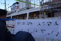 遠洋航海実習に出るりあす丸の実習生に「みなさん いってらっしゃい」と手書きの横断幕を掲げて見送る家族=宮古市の藤原ふ頭で