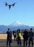 ドローンのデモ飛行に関心を寄せる参加者=甲斐市宇津谷の日本航空学園で