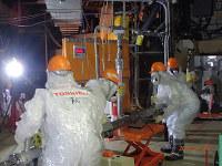 東京電力福島第1原発2号機の格納容器内にカメラを入れる作業員=東京電力提供