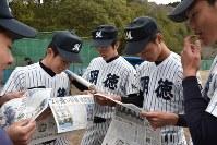 センバツ出場が決まり、本紙号外を眺める選手たち=須崎市浦ノ内の明徳義塾高校で2017年1月27日午後4時10分、松山文音撮影