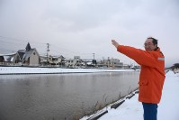 火の手が迫った川を指す土井さん。酒田大火では川岸の向こう側は焼け野原となった=山形県酒田市で