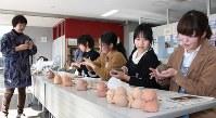 丹治陽子さん(左端)の指導を受け、地蔵づくりをする学生ら=国際医療福祉大で