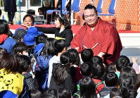 子供たちと握手などをしながら優勝報告会の会場を後にする稀勢の里関=東京都江戸川区で2017年1月28日午前11時43分、西本勝撮影
