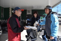 Mahmoud Jammoul, right, practices delivering newspapers in Kanuma, Tochigi Prefecture, on Jan. 16, 2017. Newspaper shop owner Kazuyo Seya is seen in the middle. (Mainichi)