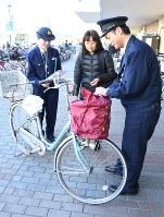 自転車の前かごにひったくり防止用カバーを取り付けてみせる警察官(右)=川口市で