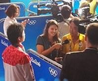 外国メディアが卓球男子の水谷隼(左)を取材する際の通訳を務める西川千春さん(右奥)=西川さん提供