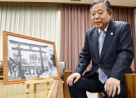 生田神社の鳥居前を走る市電の写真(1968年ごろ)を見つめ、当時を懐かしむみなと銀行の尾野俊二会長。市電はその後廃止された=神戸市中央区の同行本店で、元田禎撮影