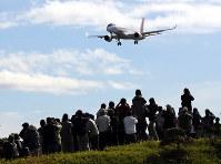 大勢の人が見守る中、初飛行を終えて愛知県営名古屋空港に着陸するMRJ=愛知県春日井市で11日午前11時1分、山口政宣撮影