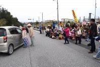 ゲート前に座り込み、工事作業員が乗った車を阻止する人々=沖縄県名護市辺野古の米軍キャンプ・シュワブ前で2017年2月6日午前8時11分、浅野翔太郎撮影