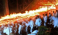 Men carrying torches dash down a stone staircase as part of Kamikura Shrine's Oto Matsuri fire festival in Shingu, Wakayama Prefecture, on the night of Feb. 6, 2017. (Mainichi)