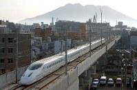 朝もやにかすむ桜島を背景に市街地を走る九州新幹線「つばめ」=上入来尚撮影