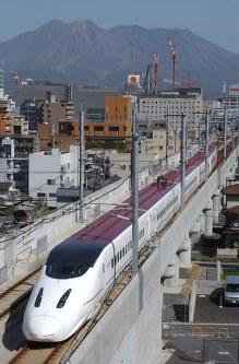 桜島をバックに鹿児島市の市街地を走る九州新幹線「つばめ」=上入来尚撮影