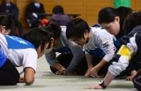床に並んだ絵札をにらむように見つめる選手たち