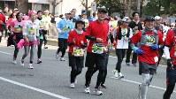 2016年2月の東京マラソンに出場した大和証券グループ本社の日比野隆司社長(中央) ※掲載にあたり写真の一部を加工しています