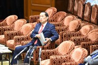 衆院予算委員会で組織犯罪処罰法改正案を巡る法務省の文書についての質問を聞く金田勝年法相(中央)。金田法相の席後方で答弁に関する説明のため待機していた同省担当者は、委員長らに注意され最後列の席に移った=国会内で2017年2月8日午後2時39分、川田雅浩撮影
