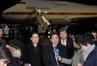 トランプ米大統領との初の首脳会談を行うため、ワシントンに向けて出発する前に記者の質問に答える安倍晋三首相(中央右)と岸田文雄外務相(同左)=東京・羽田空港で2017年2月9日午後6時53分、宮武祐希撮影