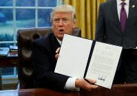 環太平洋パートナーシップ協定(TPP)から離脱する大統領令に署名して掲げて見せるトランプ米大統領=米ワシントン・ホワイトハウスで2017年1月23日 ロイター/アフロ