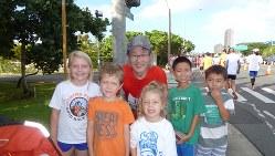 ホノルルマラソンで沿道の子どもたちと=江上剛さん提供 ※掲載にあたり写真を一部加工しています