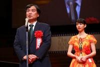 映画「この世界の片隅に」で日本映画優秀賞を受賞し、表彰式であいさつする片渕須直監督(左)。右はのんさん=川崎市幸区のミューザ川崎シンフォニーホールで2017年2月15日午後5時35分、小川昌宏撮影