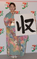 Ski jumper Sara Takahashi, clad in kimono, shows off a piece of paper with the kanji