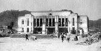(1)広島駅を南から北北東に向いて撮影。正面2階にあった待合室と出札室は爆風で倒壊。本体の屋根は押し下げられ変形、破損した。その後の類焼で駅舎は全焼、屋根も崩壊した。後方左が二葉山。駅前や構内に大勢の人影が見える(爆心地から1900メートル)=1945年8月9日、広島平和記念資料館(原爆資料館)検証