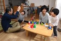 自宅のリビングで次男(左から2人目)、長女と遊ぶ栗並えみさんと夫の秀行さん。寛也ちゃんの遺影は左側の畳スペースに置かれている。栗並さん夫妻にはいつまでもかわいい3人の子どもだ=愛知県碧南市で、木葉健二撮影