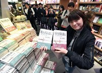 A smiling fan holds copies of Haruki Murakami's new book,