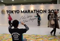 「TOKYO MARATHON 2017」と書かれた壁の前で、記念撮影するランナーたち=2017年2月24日、中嶋真希撮影