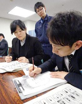 鑑識課の高橋係員(中央)から助言を受け、目撃者役(左)聞き取った特徴を基に似顔絵を作成する警察官=大阪市中央区の府警本部で、宮本翔平撮影