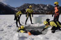 氷結した湖面に穴を開けて潜水する海上保安庁特殊救難隊の隊員たち=日光市湯元の湯ノ湖で