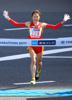 Ayaka Fujimoto crosses the finish line at the end of the women's marathon course in Tokyo's Chiyoda Ward on Feb. 26, 2017. (Mainichi)