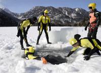 氷結した湖面に穴を開けて潜水する海上保安庁特殊救難隊の隊員たち=栃木県日光市の湯ノ湖で2017年2月24日、花野井誠撮影