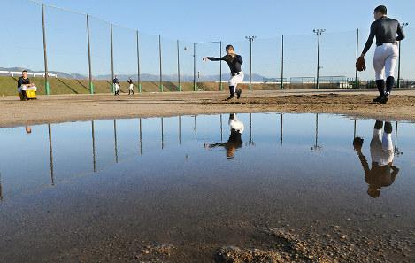 雪溶け水でできた大きな水たまりを気にしながら守備練習をする滋賀学園の選手たち=滋賀県東近江市川合寺町の同校グラウンドで、金子裕次郎撮影
