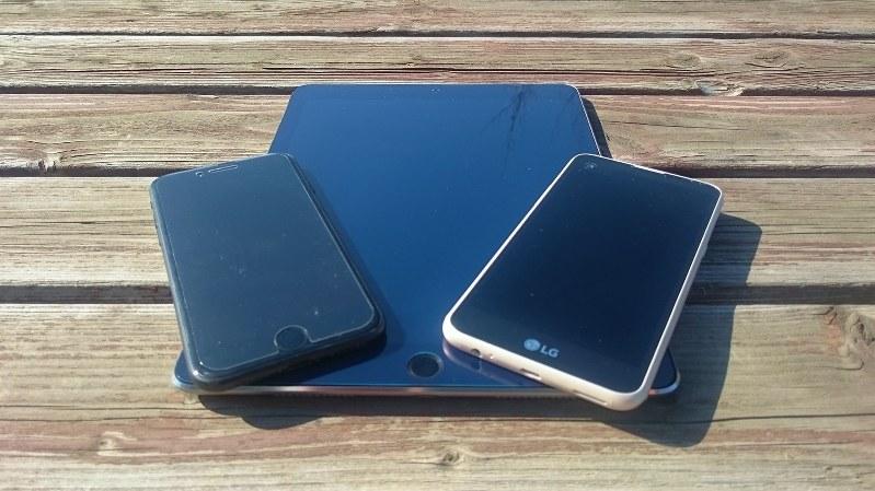 iPad pro(下)とiPhone7(左)、ジェイコムの指定端末「LG X screen」=2017年2月25日、田中学撮影