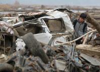 震災1カ月後、当時行方不明だった父隆芳さんの車を発見し、内部をしらべる高校1年生の佐々木奏太さん=宮城県石巻市で2011年4月11日、梅村直承撮影