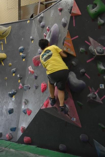 初心者用のホールドに手足をかけて壁を登っていく利用者=東京都港区港南5のROCKYボルダリングジム品川店で