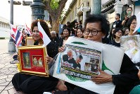 天皇、皇后両陛下を一目見ようと、タイの王宮前に集まった人たち=バンコクで2017年3月5日午後5時52分(代表撮影)
