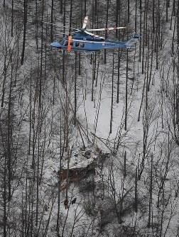 墜落した長野県の防災ヘリ(下)。上は救助にあたる長野県警のヘリ=2017年3月5日午後5時15分、本社ヘリから