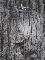 In this photo taken from a Mainichi Shimbun helicopter in a mountainous area in Nagano Prefecture on March 5, 2017, a Nagano Prefectural Government rescue helicopter is seen crashed as a Nagano Prefectural Police helicopter hovers above. (Mainichi)