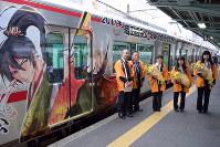 ラッピング電車の車両と大垣女子短大の学生3人(右の3人)=岐阜市の名鉄岐阜駅で