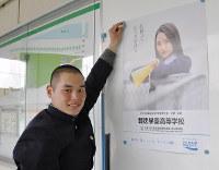 受け取ったポスターを掲示する報徳学園野球部の福島幹人マネジャー=兵庫県西宮市の同校で、山本愛撮影