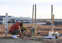 A man lays flowers at a site to commemorate those killed in the Great East Japan Earthquake, in the Yuriage district of Natori, Miyagi Prefecture, on March 11, 2017, the sixth anniversary of the disaster. (Mainichi)