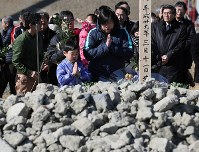 People commemorate those killed at an evacuation center by tsunami following the March 11, 2011 Great East Japan Earthquake, in Kamaishi, Iwate Prefecture, on the sixth anniversary of the disaster. Most of the evacuees in the facility when the tsunami struck died. (Mainichi)