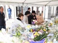 長野県消防防災航空センター前に設けられた献花台に花を手向け、手を合わせる人たち=長野県松本市空港東で2017年3月12日、小川直樹撮影