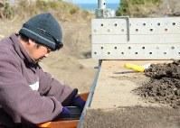 海岸で集めた土をざるに入れてふるいをかけ、次女汐凪さんの遺骨がないか捜す木村紀夫さん=福島県大熊町で、巽賢司撮影