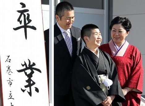 父真一郎さん(左)、母なおみさん(右)とともに、晴れ姿で大川小学校の卒業式に臨む平塚冬真さん。東日本大震災時に小学6年生だった姉小晴さんは津波にのまれ、1週間後に控えた卒業式を迎えることができなかった=宮城県石巻市で2017年3月17日午前8時37分、喜屋武真之介撮影